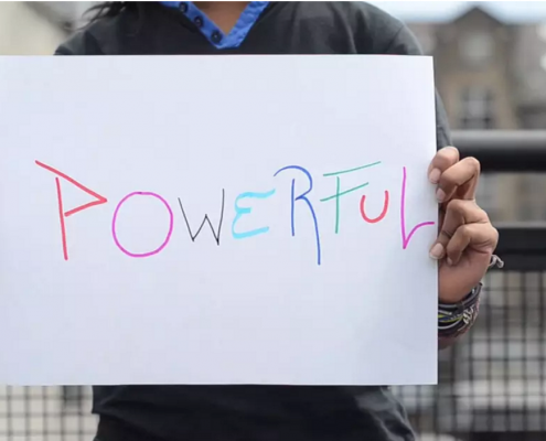 Still image from the Young, Paperless and Powerful Video showing a young person holding a poster on which the word 'Powerful' is written